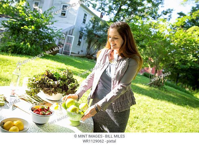 Outdoors in summer. On the farm. A woman in a farmhouse garden, preparing a table with fresh organic foods, fresh vegetables and salads and bowls of fresh fruit