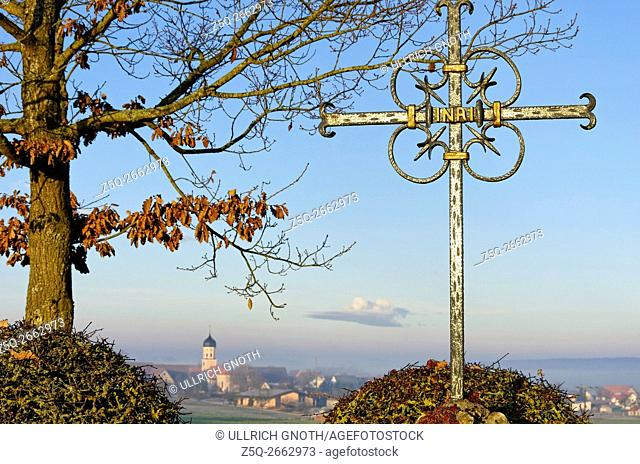 An old iron cross in front of a rural landscape with church in the background