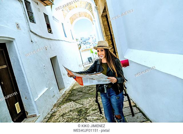 Spain, Andalusia, Vejer de la Frontera, happy young woman holding map in the alley El Callejon de las Monjas