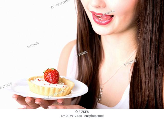 Young woman holding in her hand plate with delicious strawberry cream tart cake, licking lips, tempted to eat sweet dessert, studio, white background, isolated