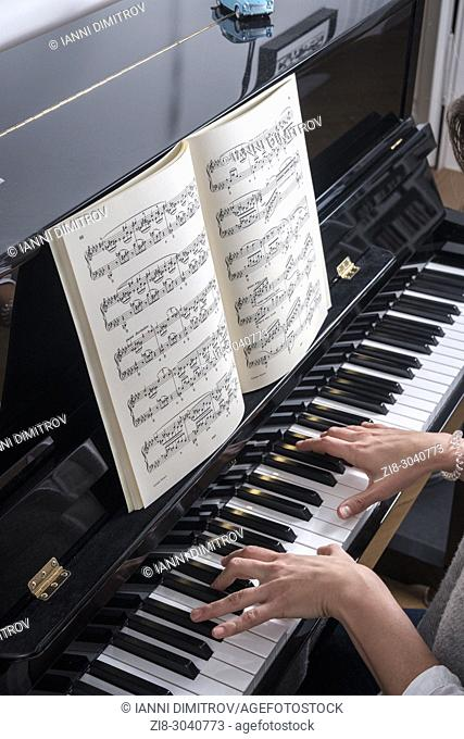 Woman plays classical music on a piano -top view