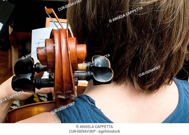 Young woman playing cello in string quartet practice, rear view