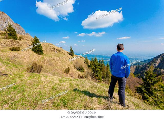 Man on top of mountain looking at the horizon. Mountain panorama