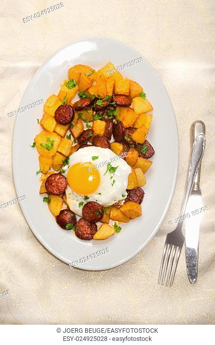 spanish meal with sliced chorizo, roasted potato, fried egg and parsley on a plate