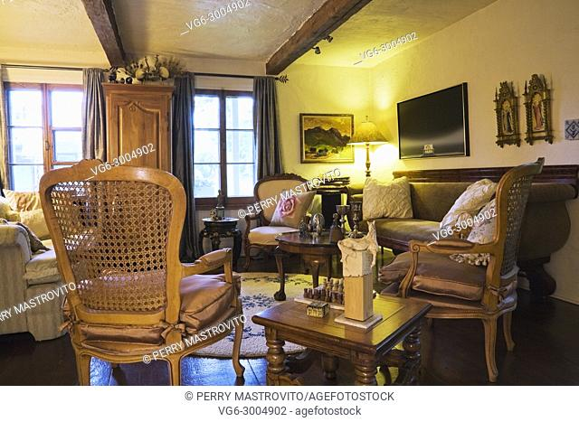 Antique wooden grid high back chairs and beige and brown sofas in the living room inside an old 1809 cottage style residential home, Quebec, Canada