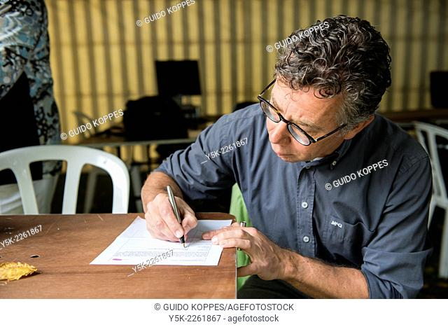 Tilburg, Netherlands. Middle aged man wearing glasses signing his model release while sitting at a table