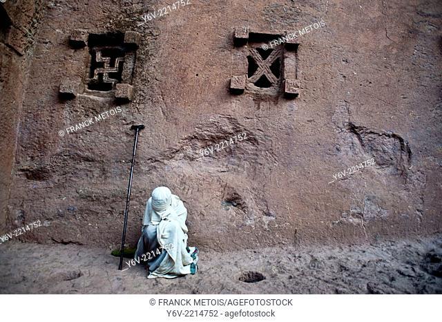 Woman praying outside of a orthodox church. Bet Maryam church at Lalibela, Ethiopia