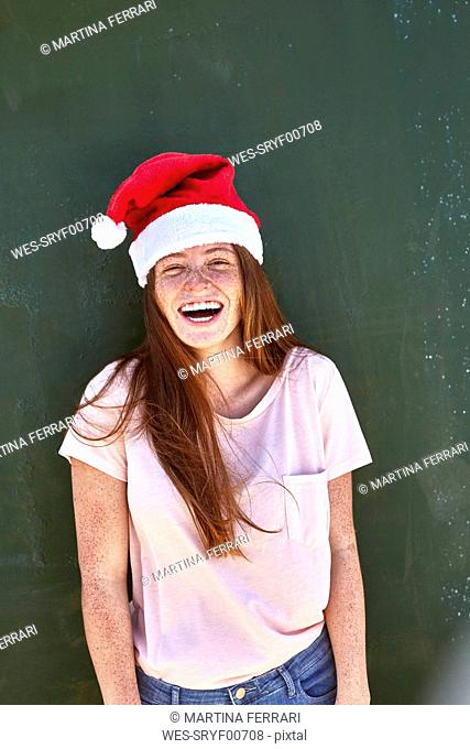 Portrait of laughing young woman wearing Christmas hat