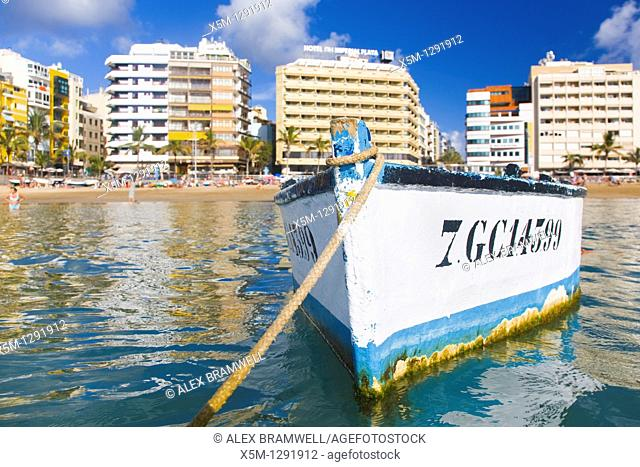 Canteras beach viewed from the sea with a traditional wooden fishing boat floating in the foreground. Las Palmas, Gran Canaria, Canary Islands