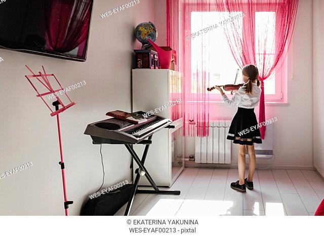 Girl playing violin at the window at home