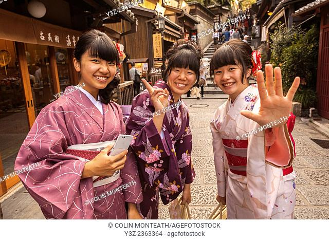 Young women dressed in traditional kimonos say farewell, Kyoto, Japan