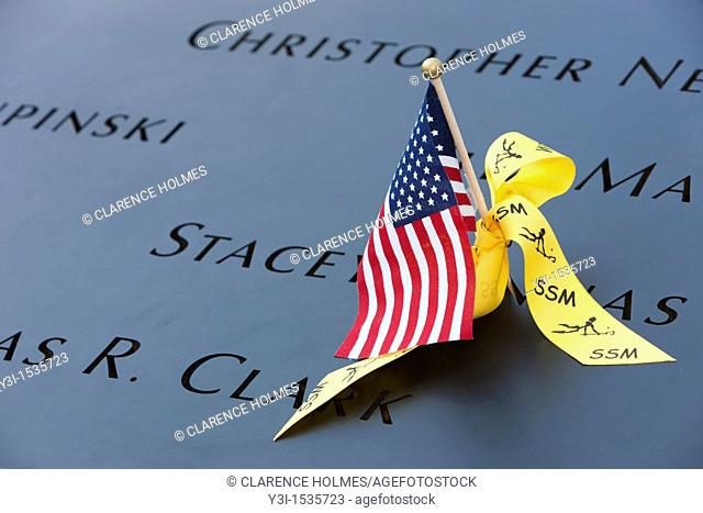 A small American flag and a yellow ribbon left on the names inscribed in the perimeter of one of the pools at the National September 11 Memorial in New York...