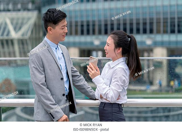 Young businesswoman and man talking in city, Shanghai, China