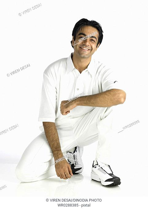 Indian bowler sitting on knee looking at camera MR702A