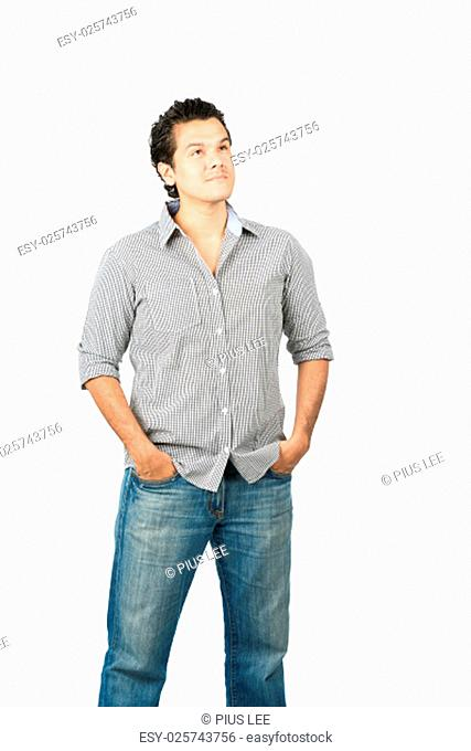 A curious, reserved latino man in casual clothes looking up away from camera with curiosity at empty copy space or product placement showing wonder, interest
