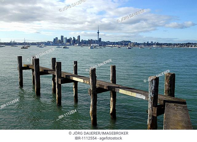 An old jetty in Northcote in front of the skyline of Auckland in the early morning, New Zealand