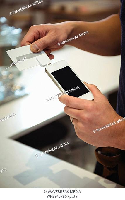 Barista swiping credit card in coffee shop