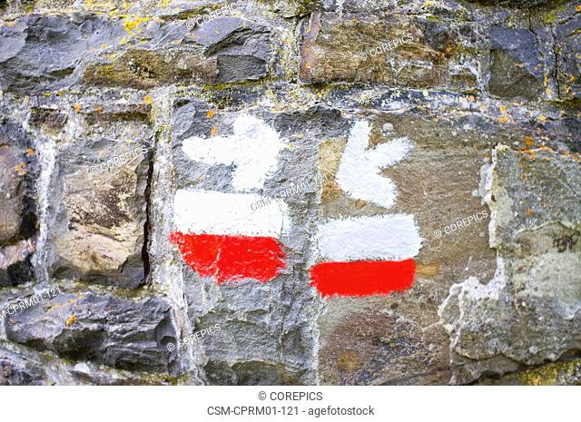 Directional arrow sign on a stone wall, with the white and red stripes of a grande randonnee hiking trail
