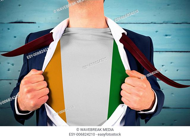 Composite image of businessman opening shirt to reveal ivory coast flag