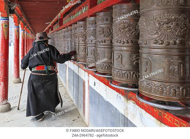 Tibetan people spinning the prayer wheels around Mani Temple (Mani Shicheng) a famous landmark in the Tibetan city of Yushu (Jyekundo), Qinghai, China