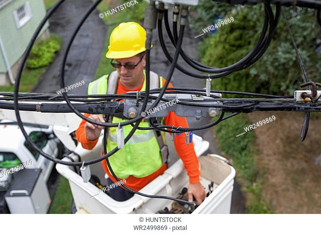 Cable lineman examining connections from bucket lift