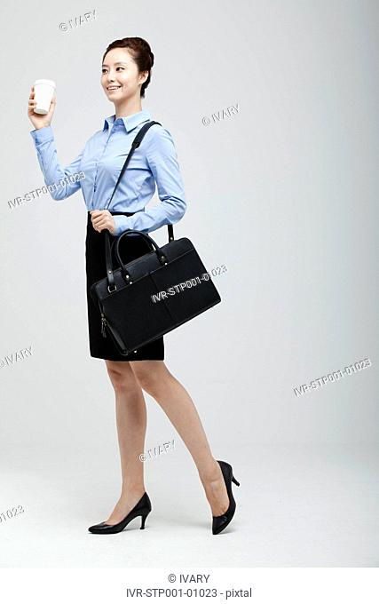 Asian Businesswoman Carrying Suitcase And Holding Takeaway Coffee In Hand