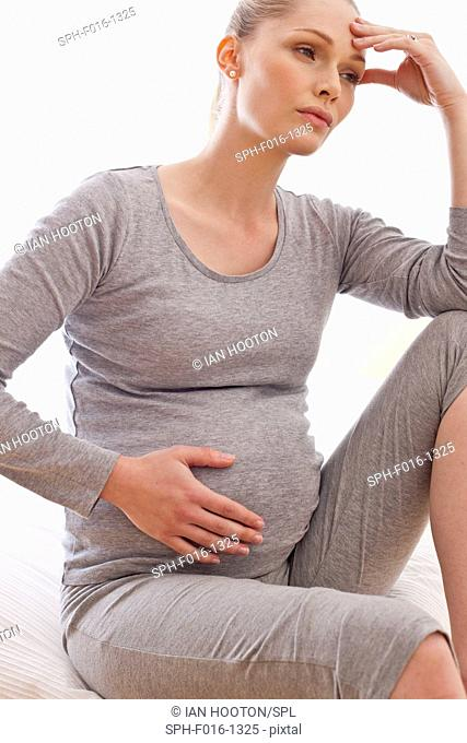 MODEL RELEASED. Pregnant woman with hand on head touching tummy