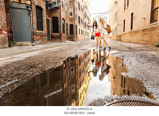 Women walking through puddle on road, Boston, MA, USA