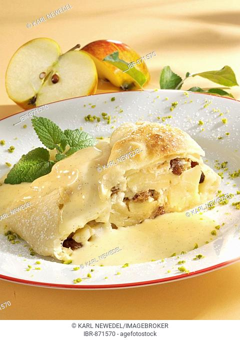 Apple strudel made from sheet pastry with vanilla sauce with pieces of pistachio and a mint garnish, apple halves