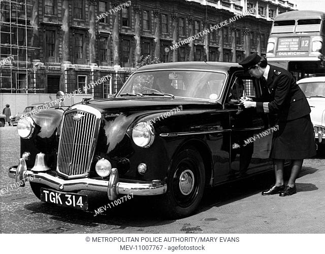 Woman police officer standing by a large black car in a London street, writing something in a notebook. Has the driver committed a driving offence