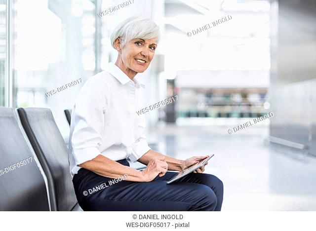 Smiling senior businesswoman sitting in waiting area using tablet