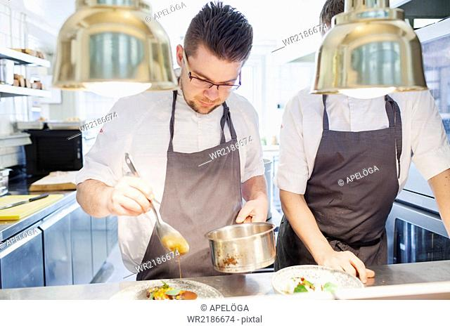 Young chefs preparing food in kitchen
