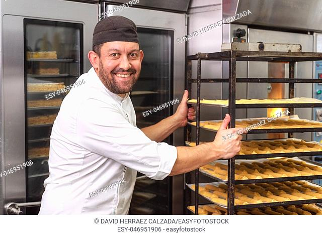 Baker putting a rack of pastries into the oven in bakery or pastry shop