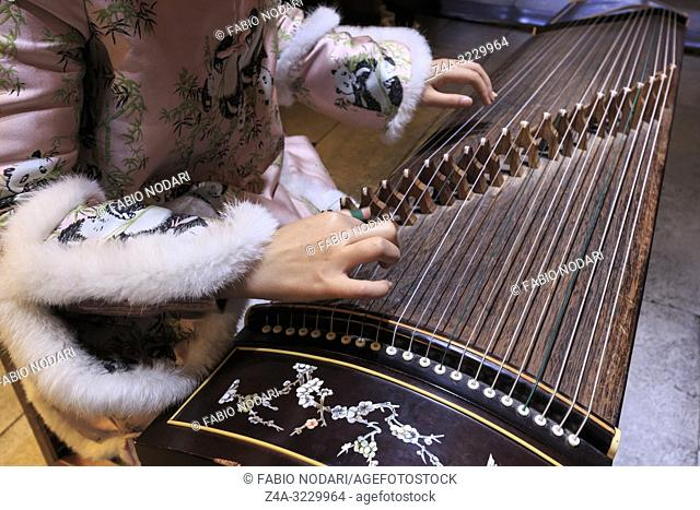 Close up of hands of a Chinese woman playing a zither, a traditional Chinese musical instrument