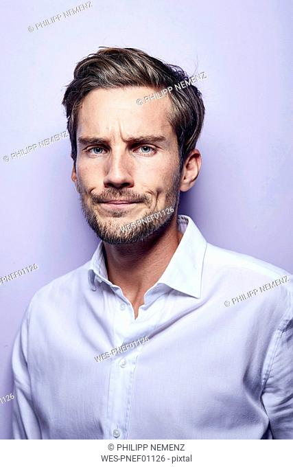 Portrait of critical young man in front of purple background