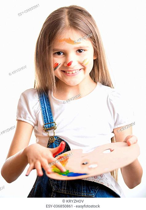 Closeup portrait of smiling little girl with painted face by different paints