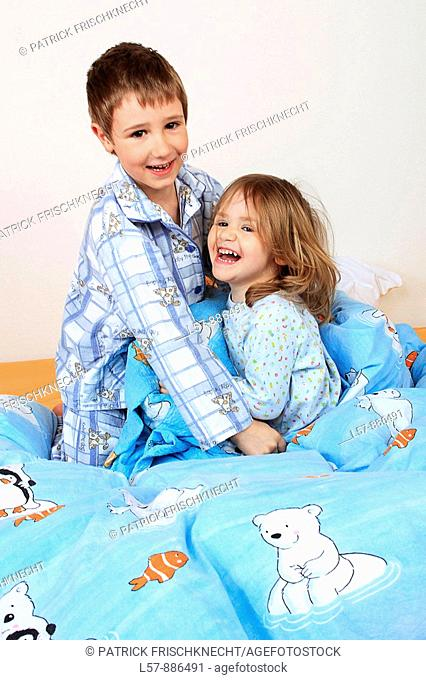 little boy and girl in bed having a pillow fight, studio, Oetwil am See, Zuerich, Switzerland