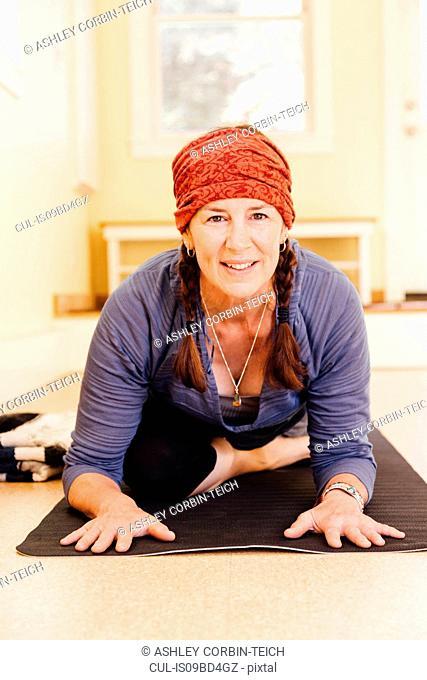 Portrait of senior woman practicing pigeon yoga pose (kapotasana) in yoga studio