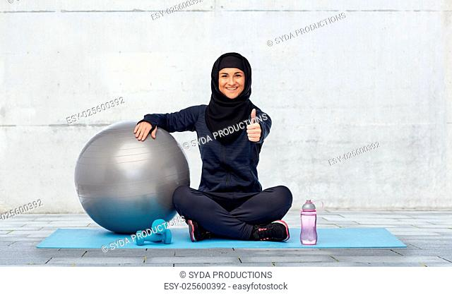 sport, fitness and people concept - happy smiling muslim woman in hijab with exercise ball, dumbbells and water bottle sitting on mat and showing thumbs up over...
