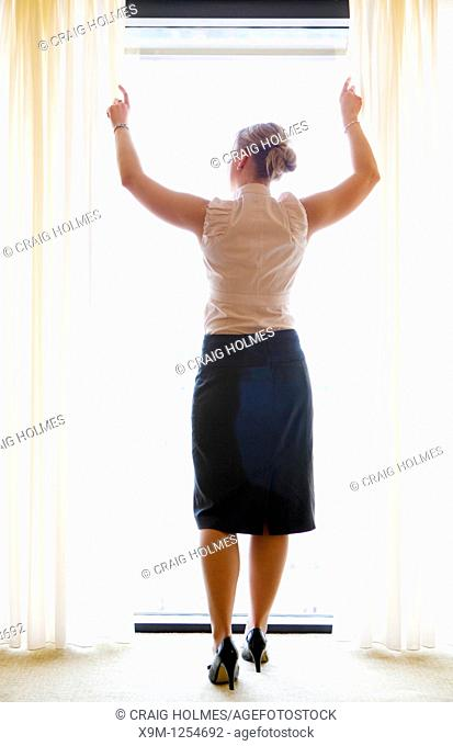 Woman in hotel suite pulling back the curtains