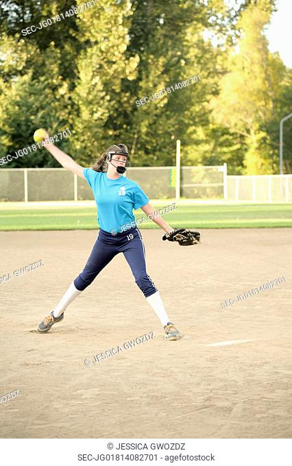 Teenager pitching soft ball