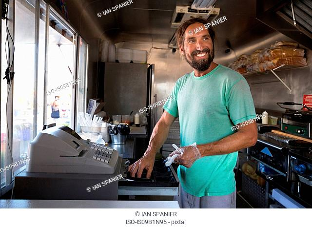 Man using cash register in fast food trailer