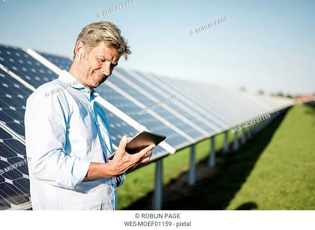 Businessman using tablet at solar park