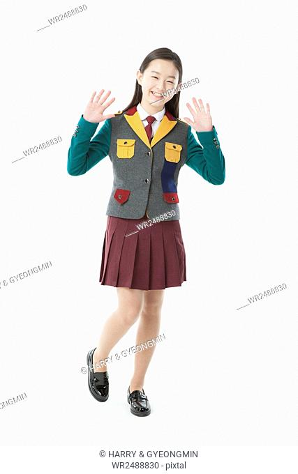 Smiling middle school girl in school uniform standing waving her hands
