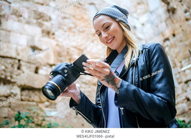 Smiling young woman looking at photos on her camera