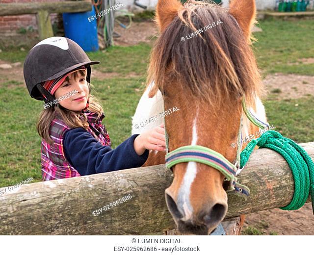 child stroking pony