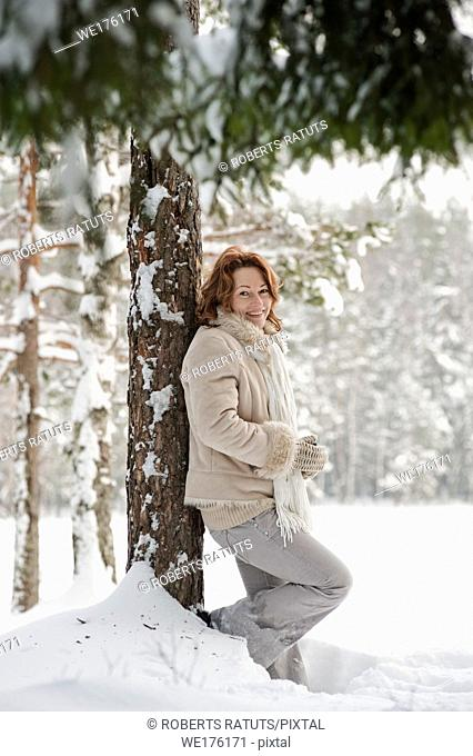 Happy red-haired woman having fun on winters day in forest. Latvia