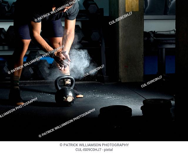 Man powdering hands before lifting kettlebell in gym
