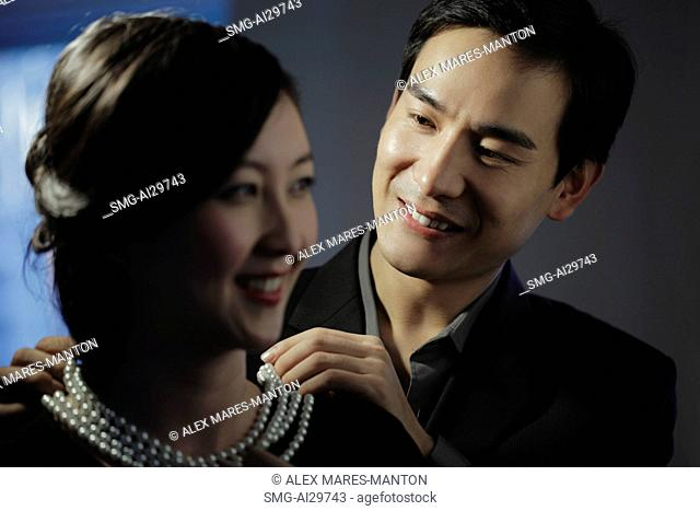 Young man putting on a pearl necklace on a woman