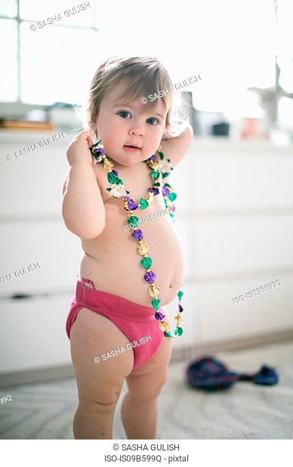Portrait of female toddler trying on bead necklace in kitchen